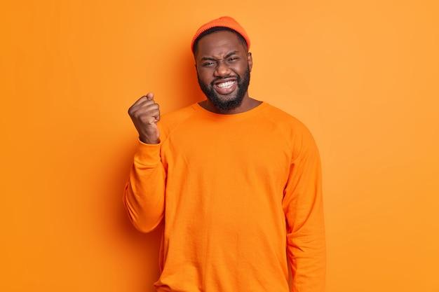 Ragazzo barbuto dalla pelle scura emotiva stringe i denti e solleva il pugno esprime emozioni negative essendo insoddisfatto di qualcosa di isolato su sfondo arancione