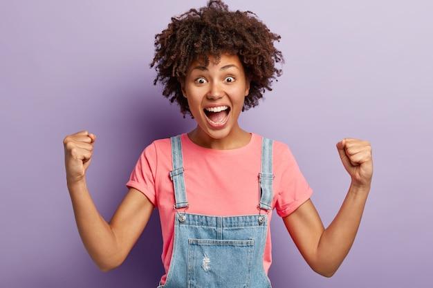 Emotiva ragazza dalla pelle scura grida per la squadra di calcio preferita, alza i pugni serrati, essendo un vero fan o sostenitore, vestita con abiti casual, posa contro il muro viola. persone e trionfo