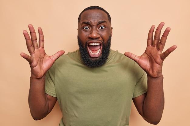 L'uomo emotivo dalla pelle scura con la barba folta tiene le mani alzate urla forte tiene la bocca aperta