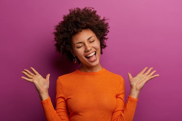 感情的な暗い肌の女性が積極的にジェスチャーし、手のひらを上げる