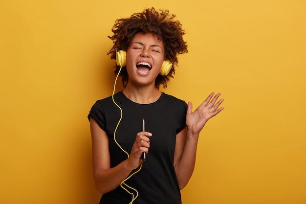 Emotiva donna dalla pelle scura con capelli afro alza il braccio, canta ad alta voce, ascolta musica che porta piacevoli ricordi isolati su giallo