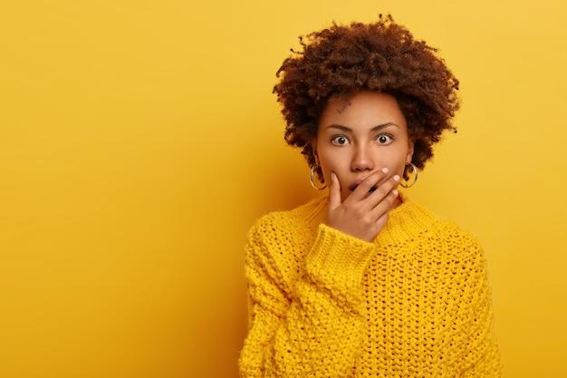 感情的な暗い肌の若い女性は驚きから息を呑み、開いた口を手のひらで覆い、カメラにショックを受けたように見え、背景のあるトーンで快適な黄色のニットセーターを着ています。
