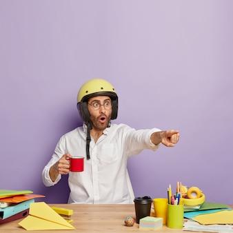 Il lavoratore maschio europeo emotivo indica la distanza, ha un'espressione spaventata, indossa un casco protettivo, tiene una tazza di caffè, lavora al desktop nel suo armadietto