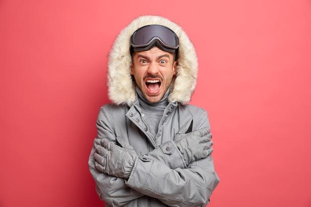 Эмоциональный европейский мужчина дрожит от холода и сердито кричит, скрестив руки, одетый в зимнюю куртку, катается на сноуборде в морозный день.