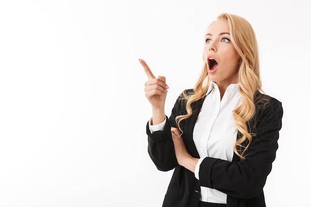 感情的な興奮しているビジネスの女性が指している白い壁に分離されたポーズします。