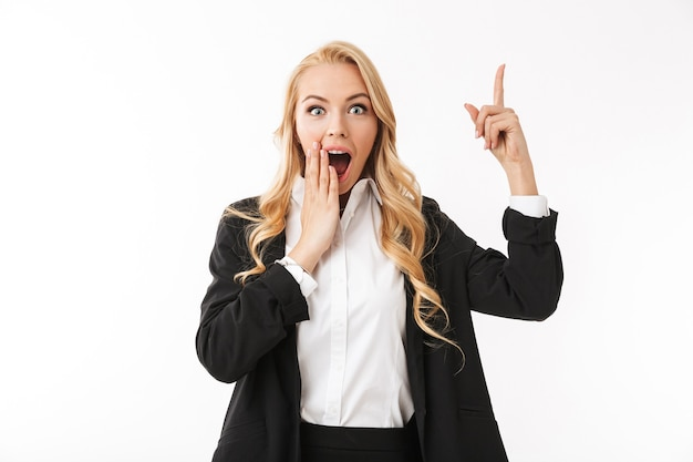 Emotional excited business woman posing isolated over white wall pointing.