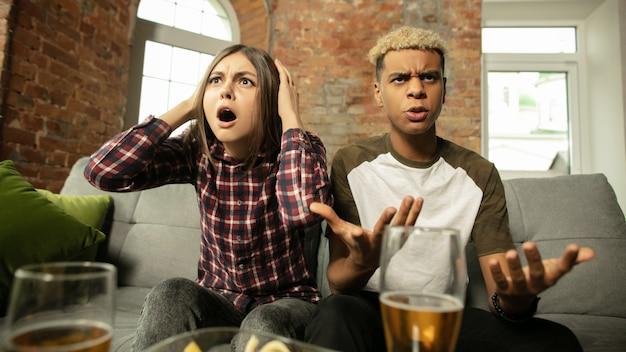 Emotivo. coppia eccitata, amici che guardano la partita sportiva, campionato a casa. amici multietnici.
