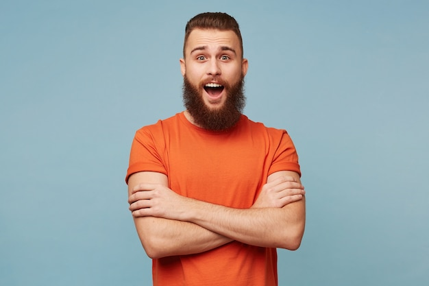 Emotional excited funny man with a heavy beard stands with arms crossed and opened mouth in surprisement dressed in red t-shirt isolated on blue