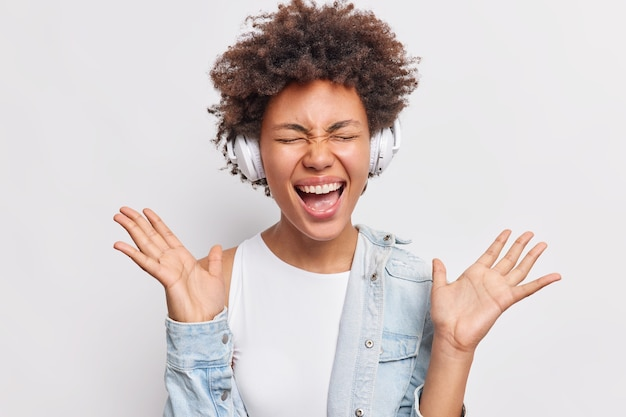Emotional excited happy millennial woman keeps palms raised exclaims