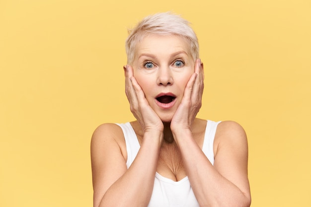 Emotional excited middle aged caucasian woman with blonde pixie hairstyle posing isolated in white tank top holding hands on her face, expressing amazement and full disbelief