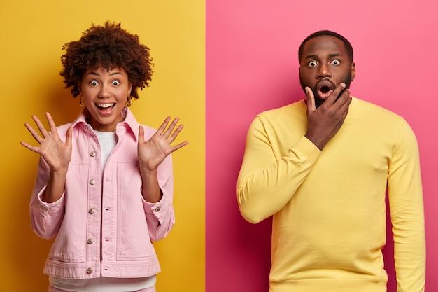 La giovane donna afroamericana emotiva ed eccitata alza i palmi delle mani, reagisce in modo impressionante, un uomo scioccato dalla pelle scura sta vicino, tiene il mento, stupito da qualcosa. concetto di persone ed emozioni