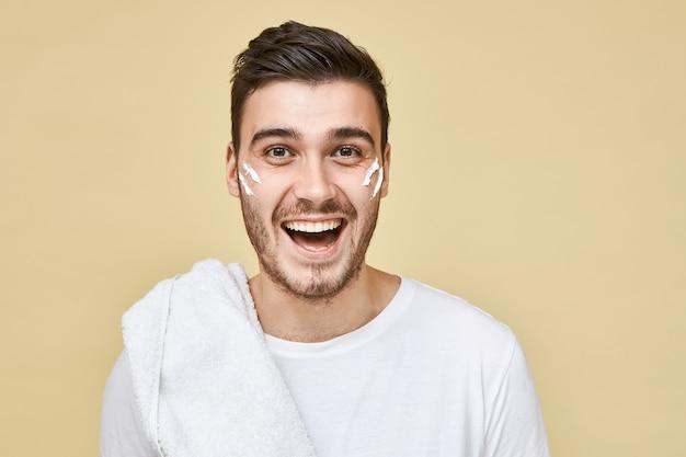Эмоционально возбужденный молодой бородатый парень позирует изолированно в футболке и полотенце на плече, собираясь побриться и принять душ после тренировки в тренажерном зале, полосы белой пены на его щеках