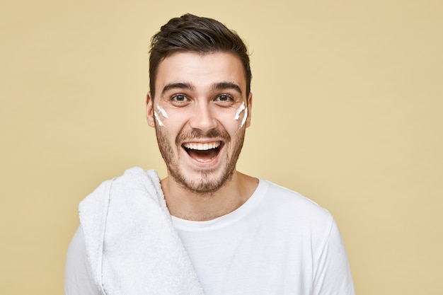 Emotional excited young bearded guy posing isolated in t-shirt and towel on his shoulder going to shave and take shower after training in gym, stripes of white foam on his cheeks