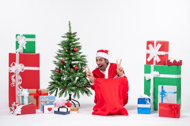Giovane emozionante emotivo vestito da babbo natale con doni e albero di natale decorato che fa gesto di vittoria su priorità bassa bianca