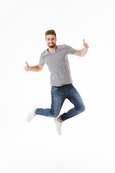 Эмоционально возбужденный молодой человек прыгает, показывая вверх жест.
