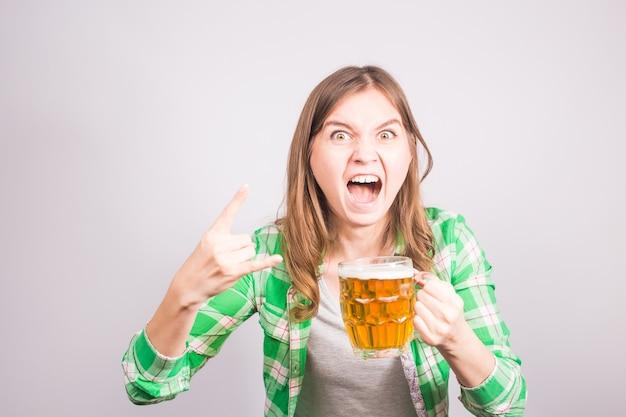 ビールを片手にエモーショナルなファン。ビールのジョッキを持つ女性