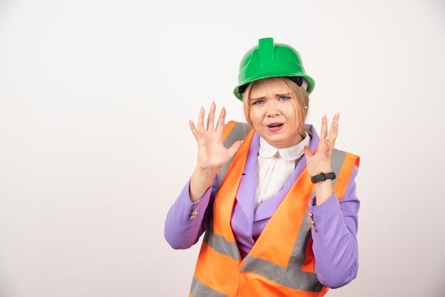 白い壁にヘルメットをかぶった感情的な女性ビルダー。