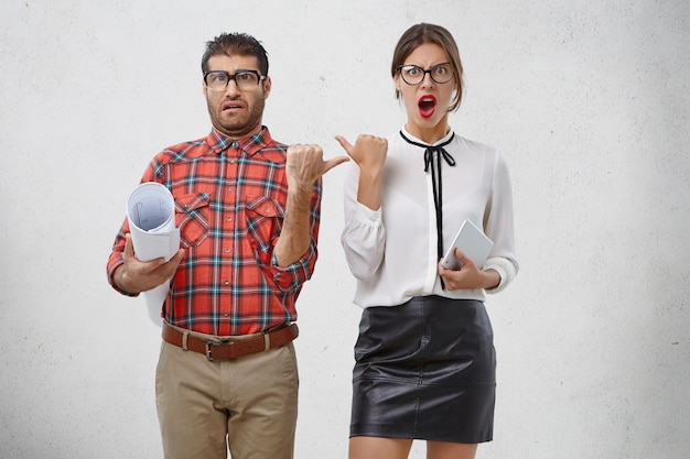 Emotional female and male coworkers point at each other with dissatisfaction,