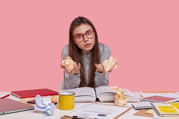 感情的な女性オタクはカメラを直接見つめ、眼鏡を見つめ、しわくちゃの紙を両手に持って、財務報告を書いています
