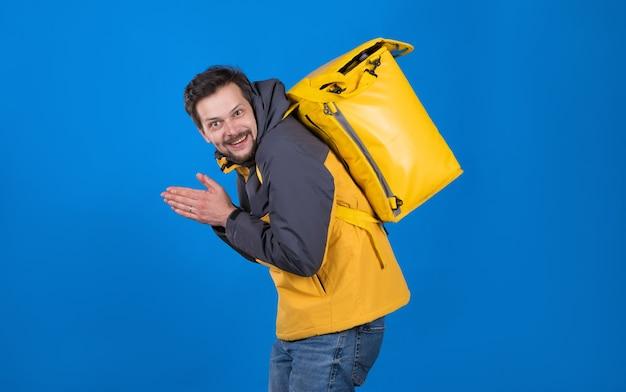 黄色い制服を着た顔にニヤリと笑い、背中に冷蔵庫のバッグを持った感情的な食品配達人が手をこすります