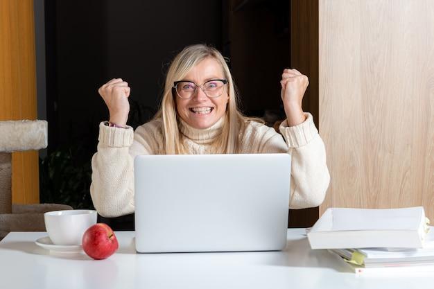 Эмоциональная женщина-фрилансер, работающая в домашнем офисе, удивленная, глядя на экран ноутбука, потрясенная полученным электронным письмом, концепция работы из дома