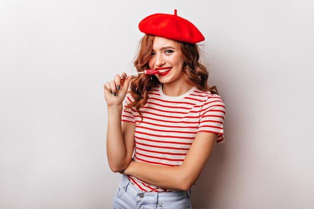 Ragazza francese emotiva in maglietta che mangia lecca-lecca. incantevole donna riccia che gode della caramella.