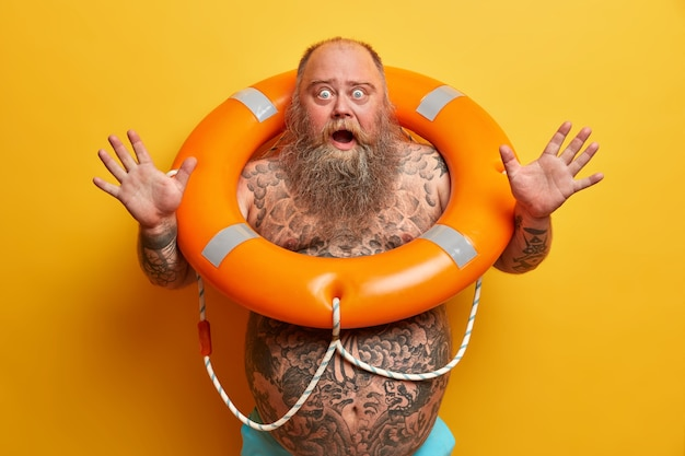 Emotional frightened bearded man raises hands and screams loudly, has bugged eyes and opened mouth, has tattooed body, stands with inflated lifebuoy, afraids of swimming, poses indoor alone.