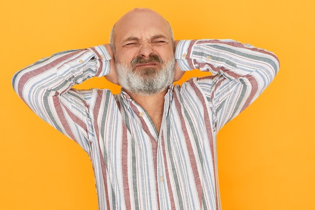 Emotional frustrated elderly european man with bald head and gray beard closing eyes and covering ears with