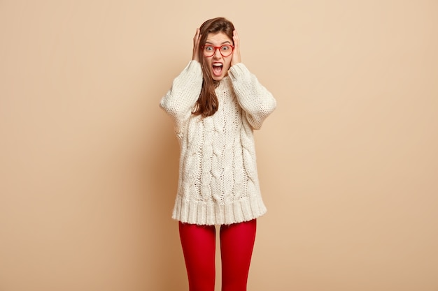 Emotiva donna frustrata piange disperatamente, copre le orecchie e grida ad alta voce, vestita con un maglione lungo bianco e collant rossi, isolato su un muro beige. odio, rabbia, aggressività e urla.