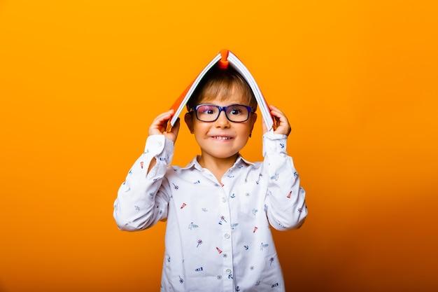 眼鏡をかけて感情的な面白い男の子はカメラに微笑んで、彼の頭、黄色の背景に本を持っています