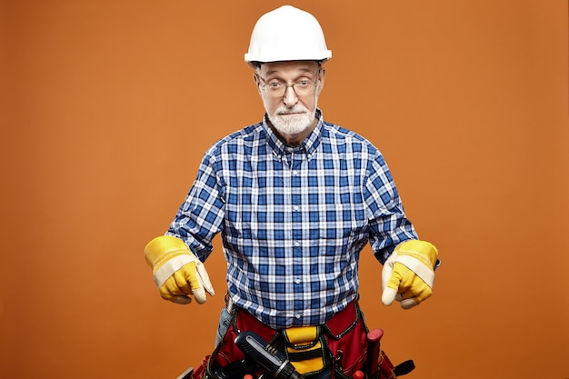 Emotional funny elderly senior house builder wearing protective helmet, safety gloves and bag with instruments around his waist having shocked surprised facial expression, pointing fore fingers down
