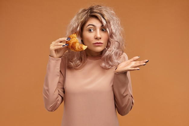 Giovane donna sorpresa divertente emotiva con i capelli rosati che esprime stupore aprendo gli occhi ampiamente, gesticolando impotente, essendo in perdita mentre si conversa al telefono