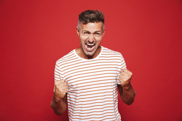 Emotional furious man in striped t-shirt screaming and showing fists isolated on red