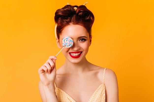 ロリポップを持って笑っている感情的な生姜の女の子。ハードキャンディーとヨーロッパの女性の正面図。