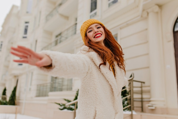 Эмоциональная рыжая девушка в зимнем наряде позирует с улыбкой. внешний портрет очаровательной рыжеволосой женщины с счастливым выражением лица.