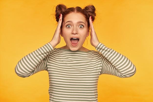 2 つのお団子を持つ感情的な生姜の女性。縞模様のセーターを着てショッキングなニュースを聞き、両手で頭を撫でる