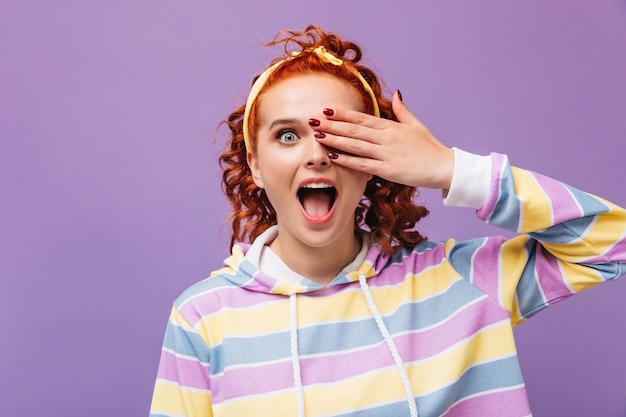 Эмоциональная девушка закрывает глаза рукой и смотрит вперед на фиолетовую стену