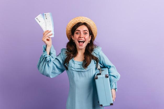 감성적 인 소녀는 비행기와 복고풍 수하물 티켓을 흥분하게 보여줍니다. 여자는 다가오는 여행을 기뻐합니다.