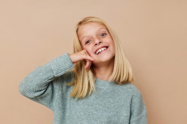 Эмоциональная девушка в свитере с гримасами позирует в студии