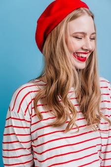青い壁で笑っているベレー帽とストライプのシャツの感情的な女の子。至福の金髪女性モデル。