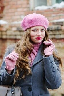 灰色のコートとピンクのベレー帽の感情的な女の子