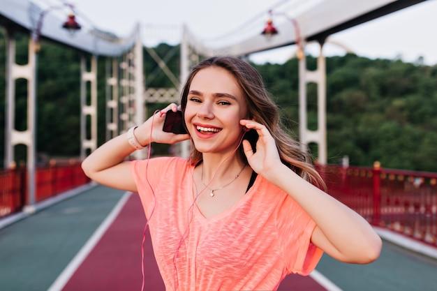 トレーニング後にお気に入りの曲を楽しんでいるピンクのtシャツの感情的な女の子。マラソンの準備をしている愛らしい白人女性。