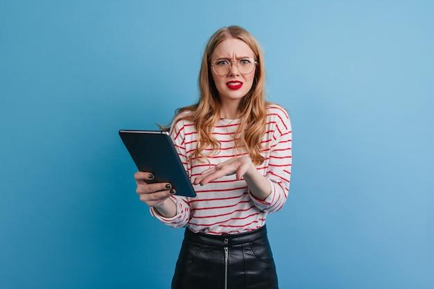 디지털 태블릿을 사용 하여 스트라이프 셔츠에 감정적 인 소녀. 파란색 배경에 고립 된 가제트와 백인 금발 여자의 스튜디오 샷.