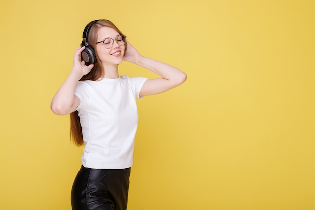 Эмоциональная девушка слушает музыку в наушниках и веселится на желтой стене