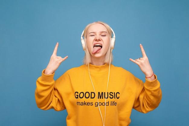 感情的な女の子は目を閉じて青のヘッドフォンで音楽を聴きます