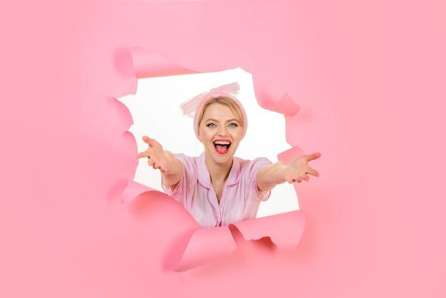 Эмоциональная девушка, глядя через отверстие в бумаге счастливая женщина с чистой кожей яркий макияж улыбающаяся девушка