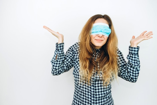 An emotional girl in a medical mask on a white wall. how to protect against coronavirus? girl in a panic because of covid 2019.