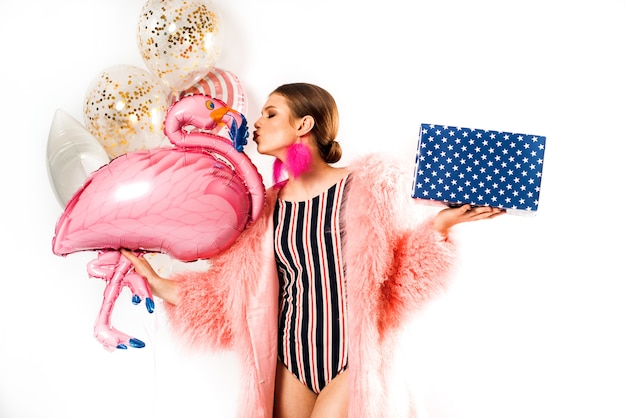 Emotional girl at a party in a red striped swimsuit and a pink fluffy fur coat with balloons.