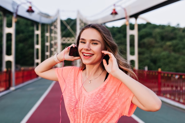 Ragazza emotiva in maglietta rosa che gode della canzone preferita dopo l'allenamento. adorabile donna caucasica preparando per la maratona.