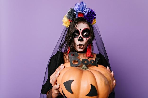 感情的な女の子は彼女の前に巨大な装飾されたカボチャを持って「ブー」と叫びます。頭蓋骨の形で描かれた黒い花嫁の肖像画。